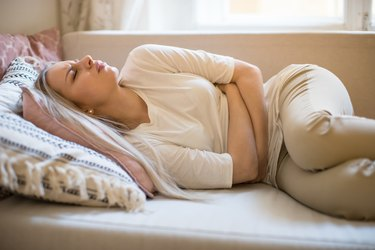 woman suffering from stomach pain, feeling abdominal pain or cramps, lying on sofa. Period menstruation