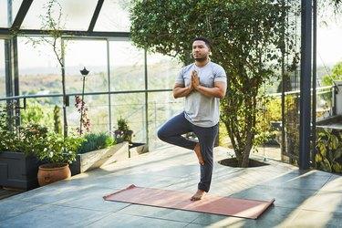 Man doing the tree pose balance exercise, as a natural remedy for vertigo