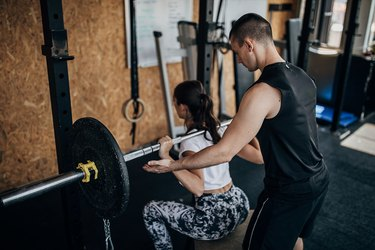 Male personal trainer assisting a woman doing a barbell back squat at the gym