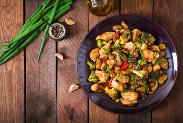 Stir fry with chicken, mushrooms, broccoli and peppers on wooden table