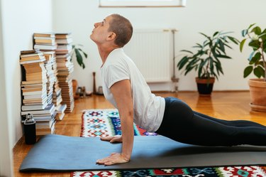 woman performing the cobra yoga pose at home on a mat