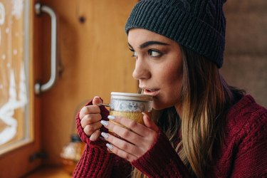 woman with hat and sweater drinking cup of green tea