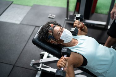 black woman doing an incline bench press in gym with mask