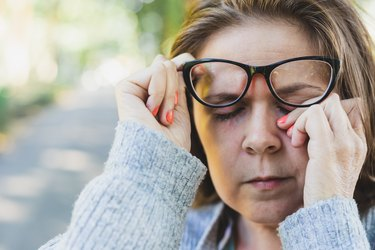 woman whose eyes are always red rubbing her eyes outdoors