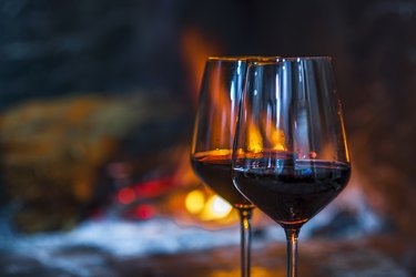 Two glasses of red wine in front of the fireplace fire