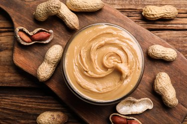 resveratrol-rich peanut butter in glass bowl on wooden table with peanuts surrounding