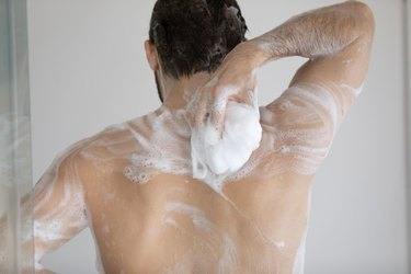 Man washing back with soap in the shower