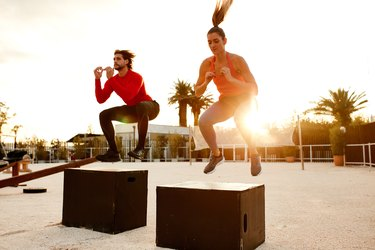 a man and woman doing box jump exercises outside at sunset