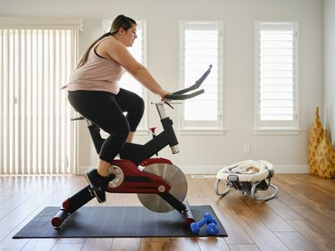 woman exercising on a stationary bike for cardio workout at home