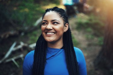 smiling woman with protective hairstyle exercising outdoors