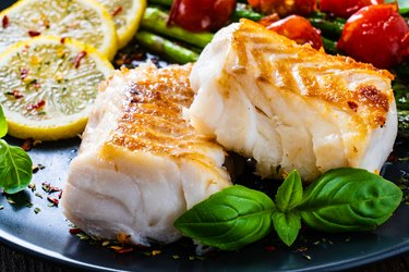 Cooked cod fillet with lemon and vegetables on plate