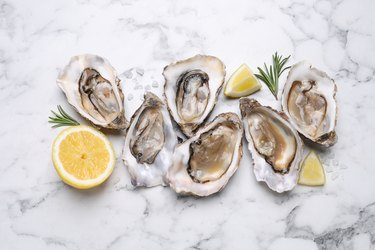 Zinc-rich raw oysters with lemon and rosemary on white marble table.