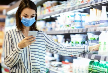 Woman in face mask using smartphone standing in store