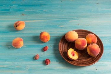 A few ripe, velvety peaches on blue wooden table. Sunny