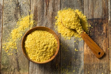 overhead photo of wooden bowl and spoon of raw yellow nutritional yeast on wooden table