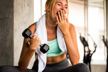 Woman lifting a dumbbell and yawning during her workout
