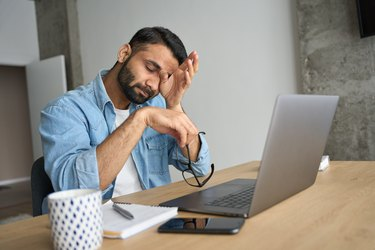 Young tired Hispanic indian student rubbing eyes sitting at desk with laptop.