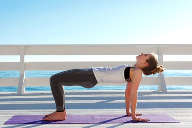 woman doing the crab walk exercise outside in front of water and white fence on yoga mat