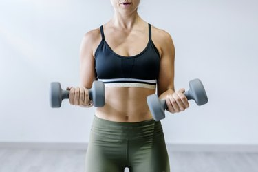 Woman holding dumbbells at gym