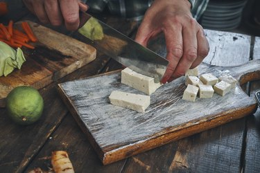 Cutting Tofu on Wooden Cutting Board before cooking it