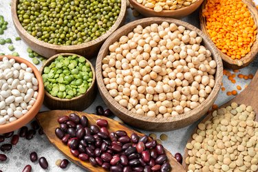Different legumes. Mung beans, red and white beans, lentils, peas and chickpeas in wooden bowls on the light grey kitchen table. Beans closeup. Vegetarian food