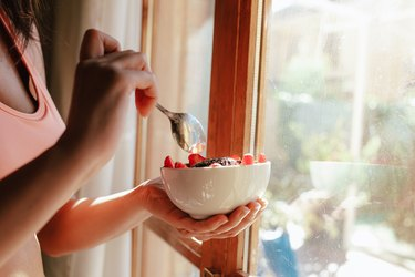 woman eating breakfast bowl of fruit yogurt seeds and chocolate
