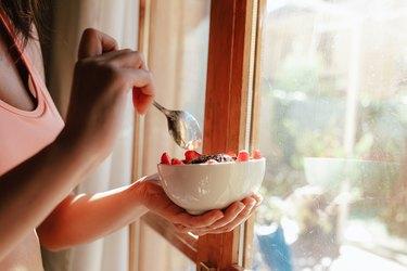 woman eating breakfast bowl of fruit yogurt seeds and chocolate