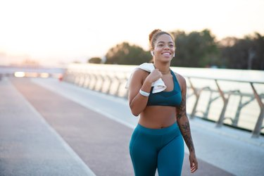 woman running outside on a pier, wearing a sports bra to prevent saggy breasts