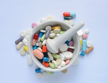 Heap of medicine pills and capsules on a white background.