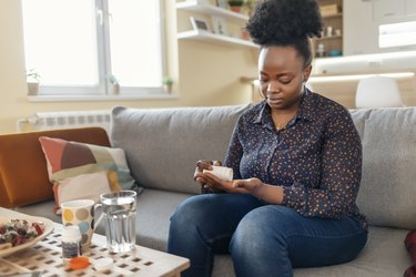Black woman sitting on grey couch pouring Synthroid pills stored in a white bottle into her hand