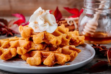 Pumpkin spice waffles with whipped cream for Thanksgiving Day.