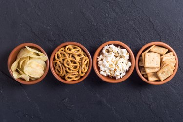 top view of small bowls filled with crunchy snack foods to avoid after wisdom tooth removal