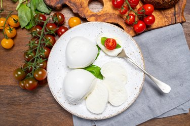Cheese collection, eating of white soft Italian cheese mozzarella, served with red cherry tomatoes, fresh basil leaves