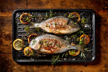 Grilled fish (a major food allergen) with the addition of spices, herbs and lemon on the grill plate located on a wooden background,  top view.