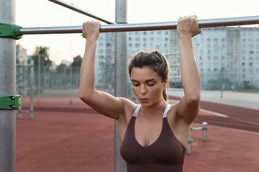 Strong woman athlete doing chin-ups during calisthenics workout
