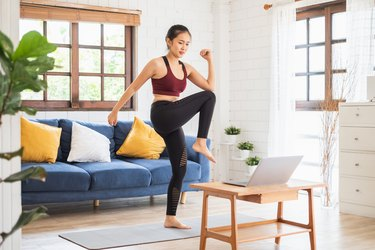 Asian woman following a low-impact cardio workout on her laptop in her living room
