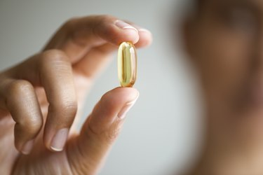 A woman holding a fish oil supplement capsule