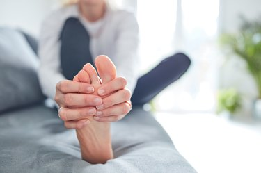 Closeup of woman sitting on a couch and massaging foot and broken toe