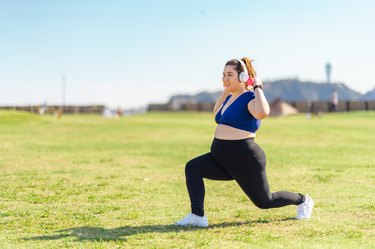 Young female athlete doing muscle trainings with dumbbells at public park