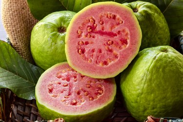Closeup of a red vitamin A-rich guava cut in half, in the background several guavas and green leaf.