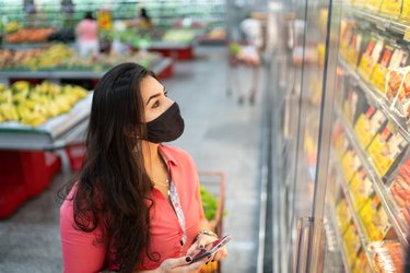 Woman wearing face mask shopping in the supermarket for Weight Watchers frozen meals
