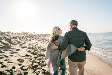 Back view of an older couple walking on the beach to lower inflammation