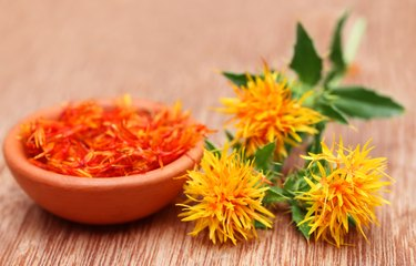 three safflower flowers and a bowl of petals on wooden background