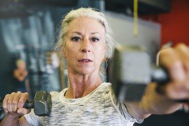 Caucasian woman lifting dumbbells in gymnasium