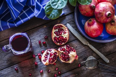 vitamin K-rich pomegranate juice and pomegranate fruits in blue bowl on a wooden table