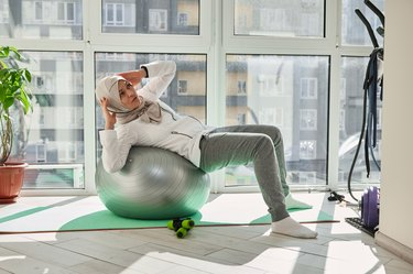 woman in hijab doing stability ball bicycle crunches in front of windows