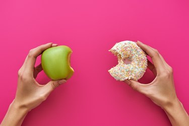 Hands holding an apple and a donut to show the concept of good vs bad food