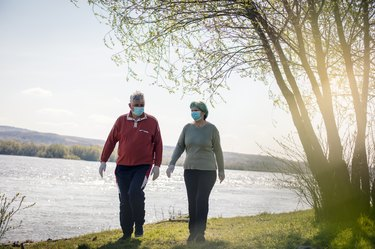 older adults walking outside for exercise to reduce blood pressure outside with face masks