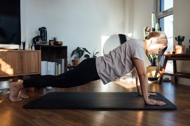 Young woman doing push-ups on exercise mat at home