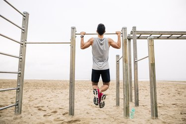 Young man doing pull-ups on the beach